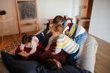 Mutter und Vater liegen auf dem Bett und Kinder spielen auf ihnen