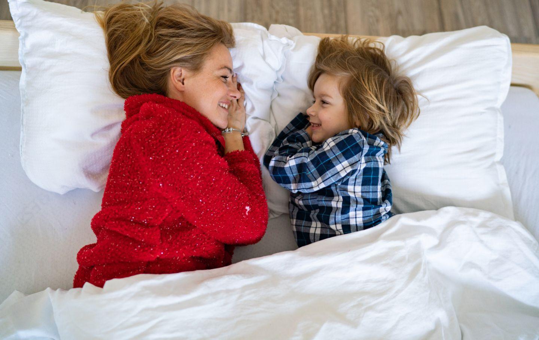 Mutter und Sohn liegen im Bett und schauen sich an