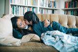Mutter liegt auf Sofa und wird von Sohn geküsst