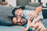 Vater liegt mit Sohn auf Sofa