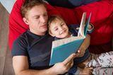 Vater liest Sohn aus einem Buch vor