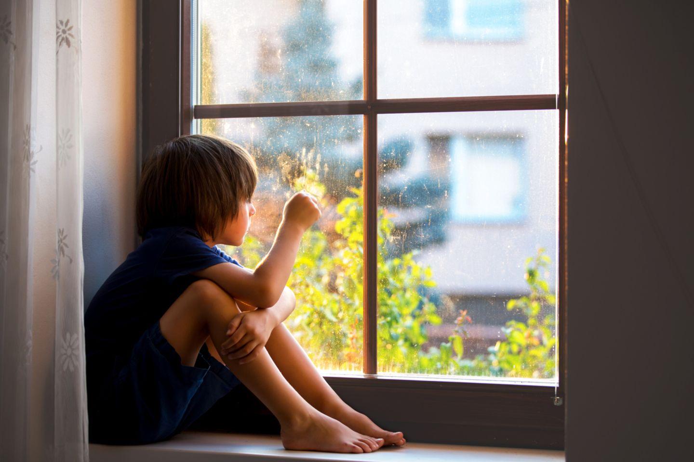 Ein Junge schaut sehnsüchtig aus dem Fenster und versucht mit dem Social Distancing klarzukommen.