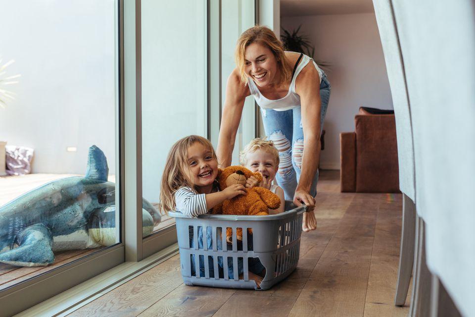 Eine Mutter spielt drinnen mit ihren zwei Kindern und einem Wäschekorb