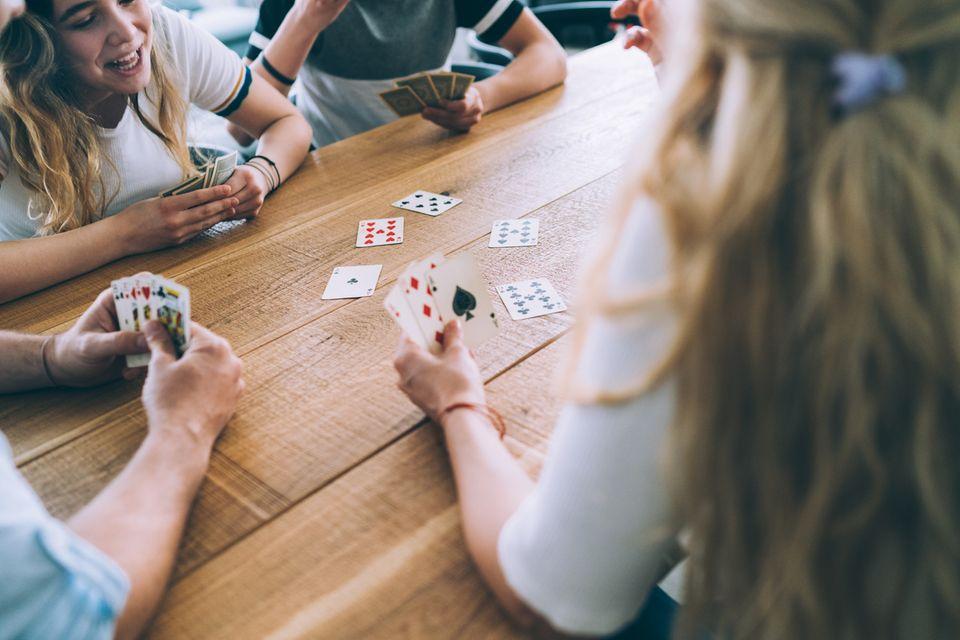 Eine Familie spielt ein Kartenspiel am Esstisch