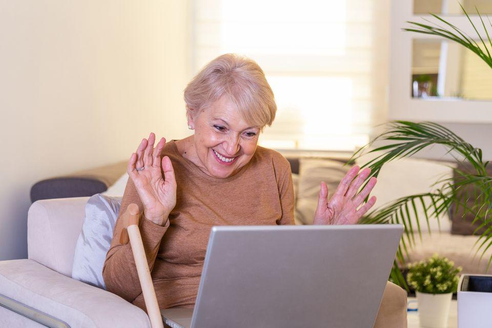 Eine Oma freut sich mit ihren Enkeln über Video-Chat zu kommunizieren