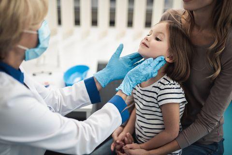 Ein Mädchen sitzt auf dem Schoß der Mutter und wird von einer Kinderärztin mit Schutzkleidung untersucht