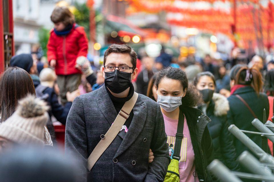Menschen, die eine Gesichtsmaske tragen, um sich wegen der Epidemie zu schützen