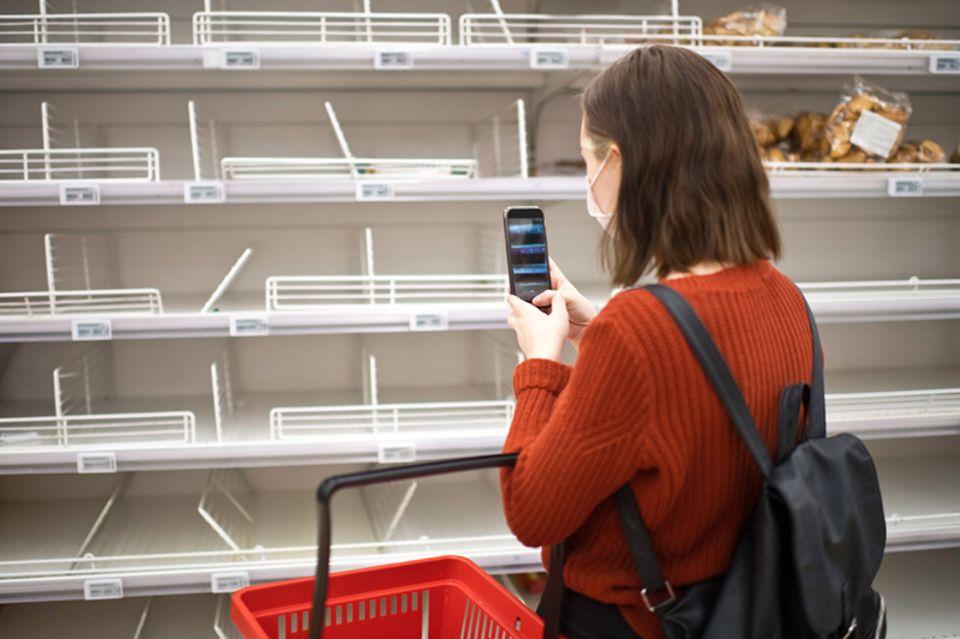 Junge Frau steht vor leerem Regal in einem Supermarkt und macht ein Foto mit dem Smartphone