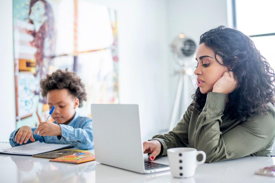 Mutter stellt Elterngeldantrag und arbeitet am Laptop, Kind sitzt daneben