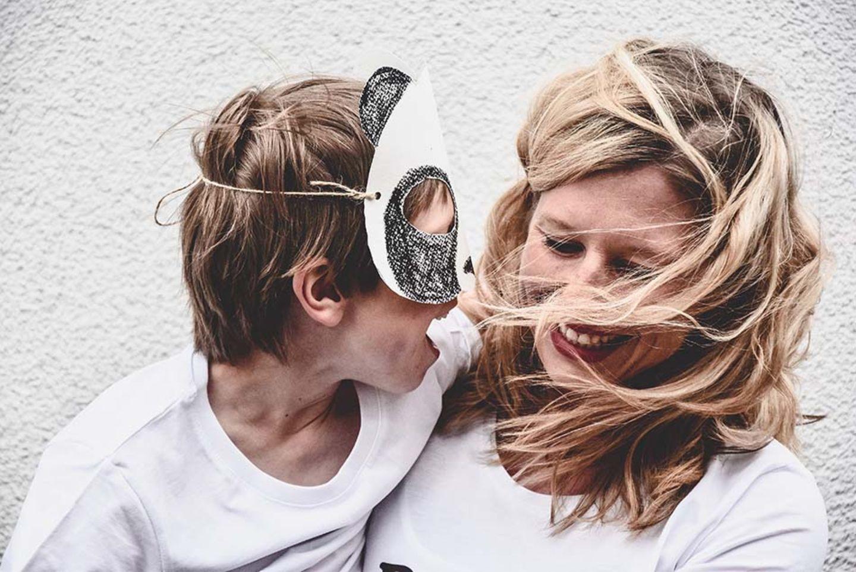Laura Fröhlich hält ihr Kind auf dem Arm, das eine Maske trägt