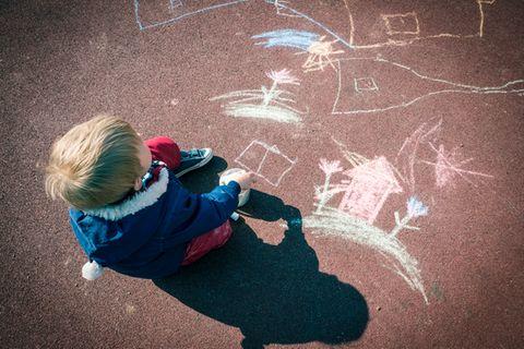 Ein kleiner Junge hat auf der Straße mit Kreide bunte Bilder gemalt
