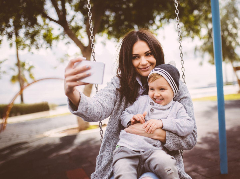 Eine Mutter sitzt mit ihrem Sohn auf dem Schoß auf einer Schaukel und macht ein Foto mit dem Handy