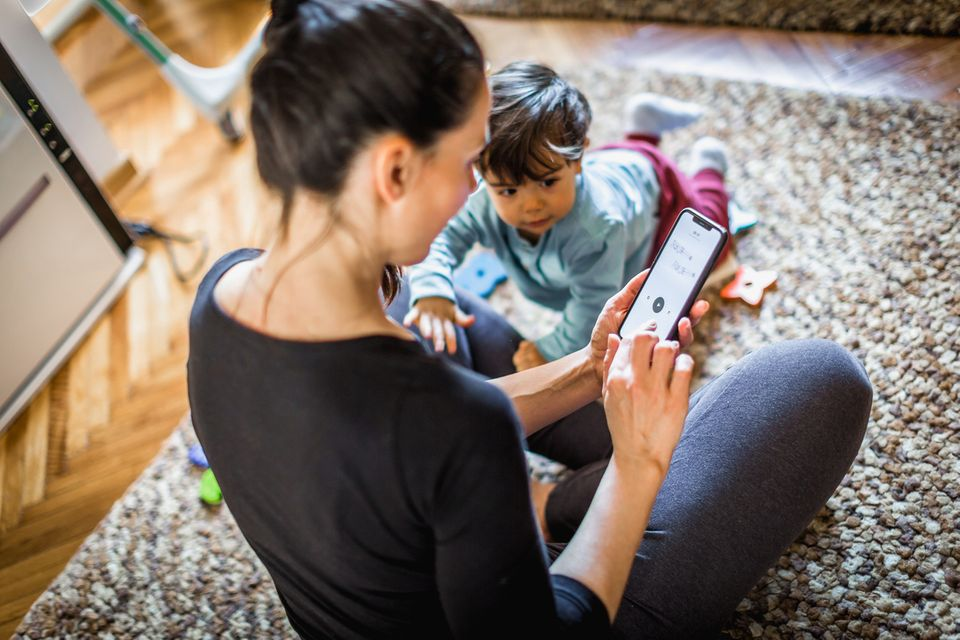 Eine Mutter sitzt auf dem Boden und öffnet eine App, ihr Kleinkind krabbelt auf sie zu