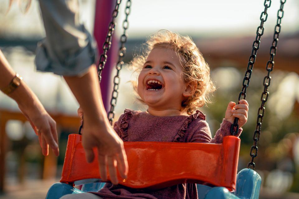 Ein Kleinkind sitzt auf der Schaukel und lacht ausgelassen