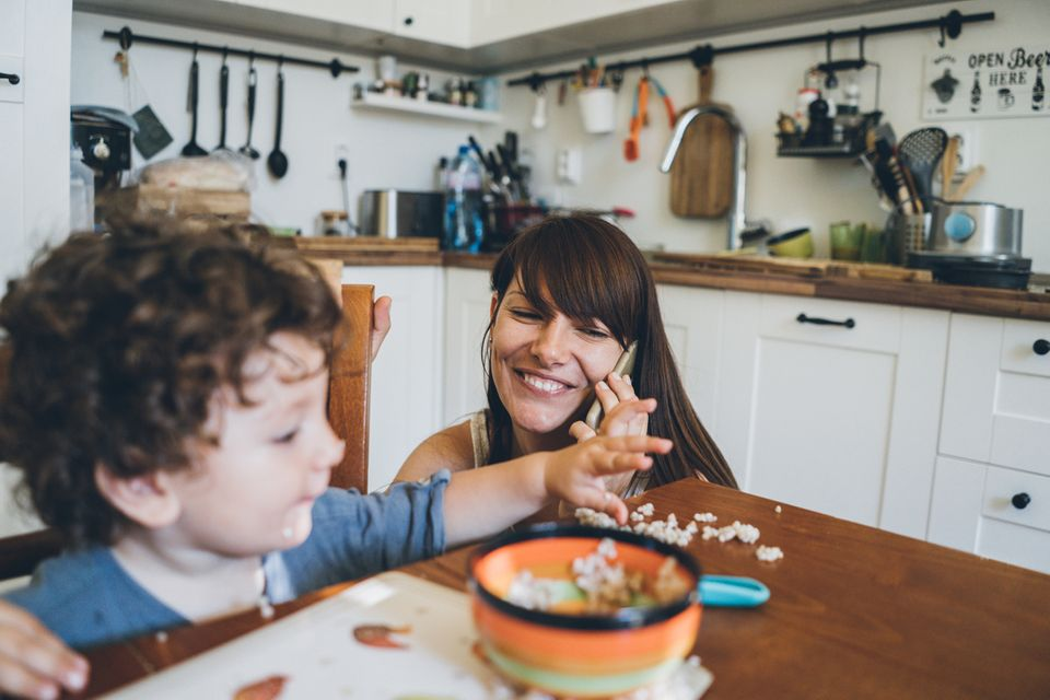 Eine Mutter hockt vor dem Küchentisch und telefoniert, ihr Sohn manscht mit seinem Essen