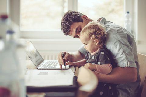 Ein Vater hat seine Tochter auf dem Schoß und arbeitet am Laptop