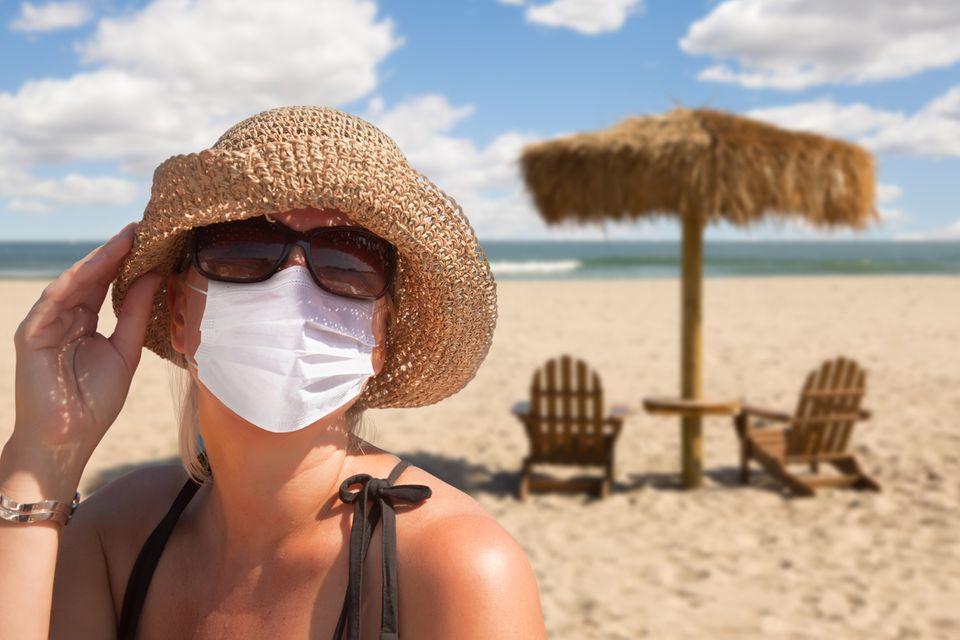 Frau mit Mundschutz am Strand