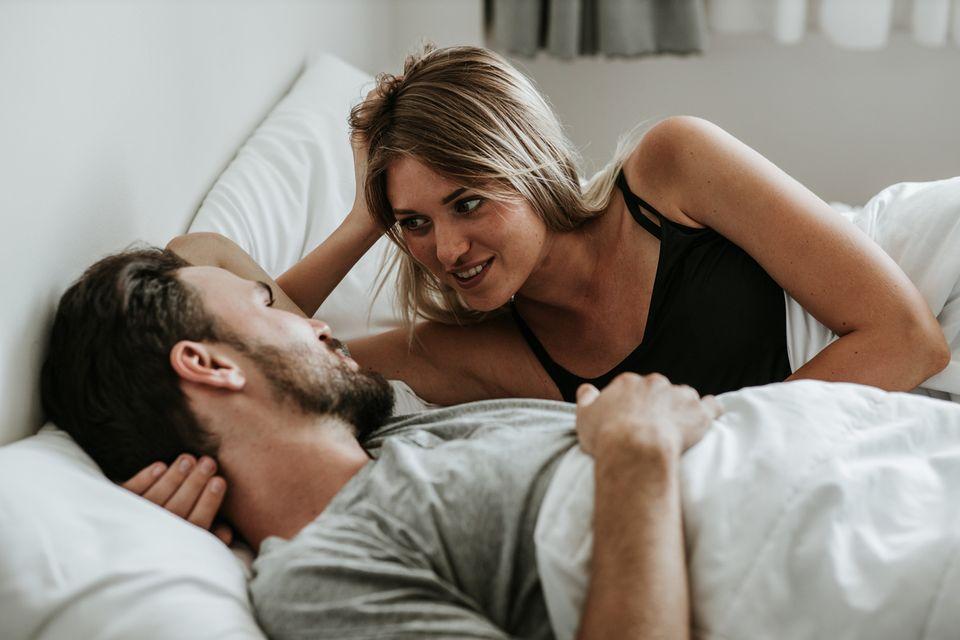 Ein Mann und eine Frau liegen im Bett und unterhalten sich