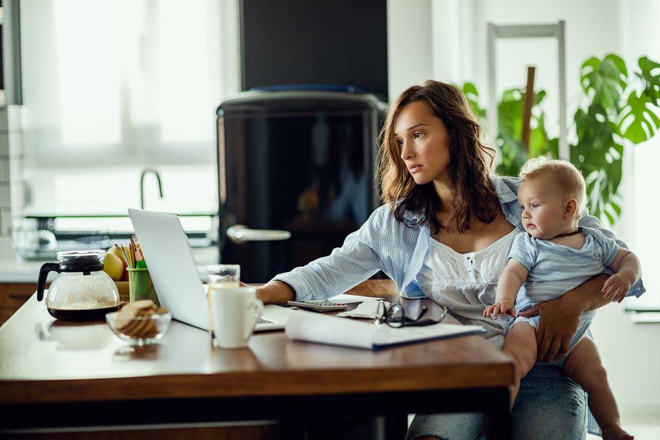 Mutter mit Baby auf dem Schoß arbeitet am Laptop