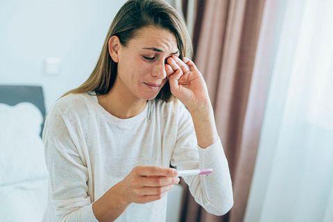 Frau weint Schwangerschaftstest