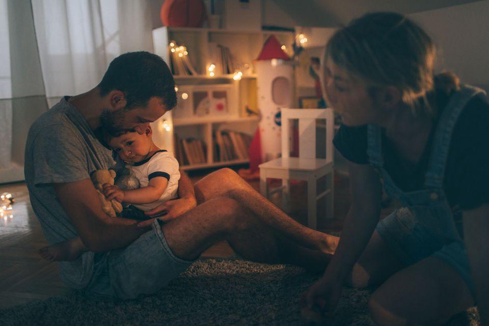 Ein Vater hält seinen kranken Sohn im Arm, die Mama sitzt daneben