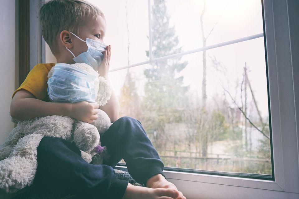 Junge mit Mundschutz schaut aus dem Fenster