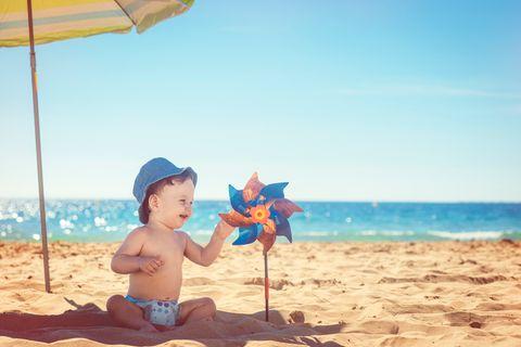 Baby-sitzt-unter-Sonnenschirm-am-Strand