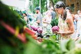 Frau steht am Marktstand und schaut sich Gemüse an