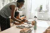 Eierkartons auf dem Tisch neben Mutter und Sohn, die am Laptop nach Rezepten suchen.