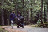 Eltern-mit-Kinderwagen-machen-einen-Spaziergang