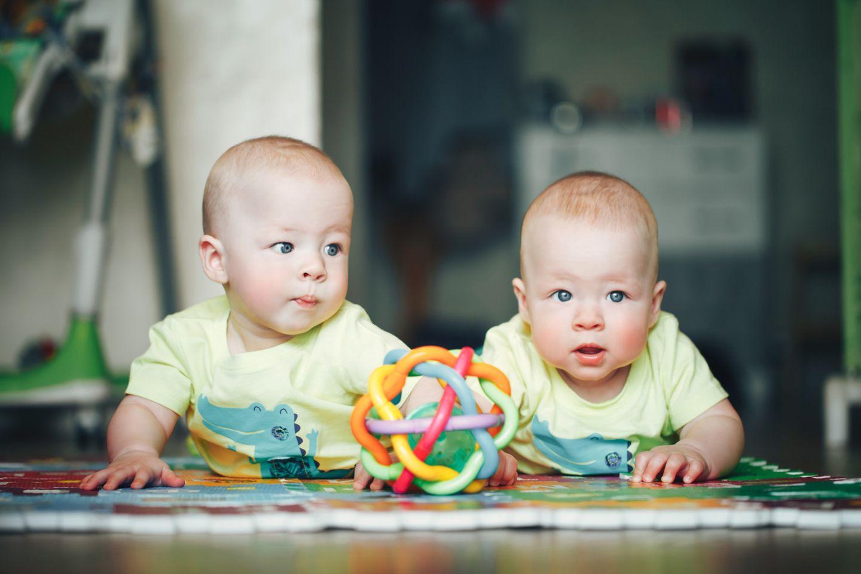 Zwillinge-liegen-auf-dem-Boden-mit-Spielzeug