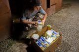 Junger Mann sitzt nachts mit Stirnlampe vorm Container und guckt sich die geretteten Lebensmittel an
