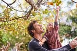 Vater trägt Tochter, die einen Apfel vom Baum pflückt