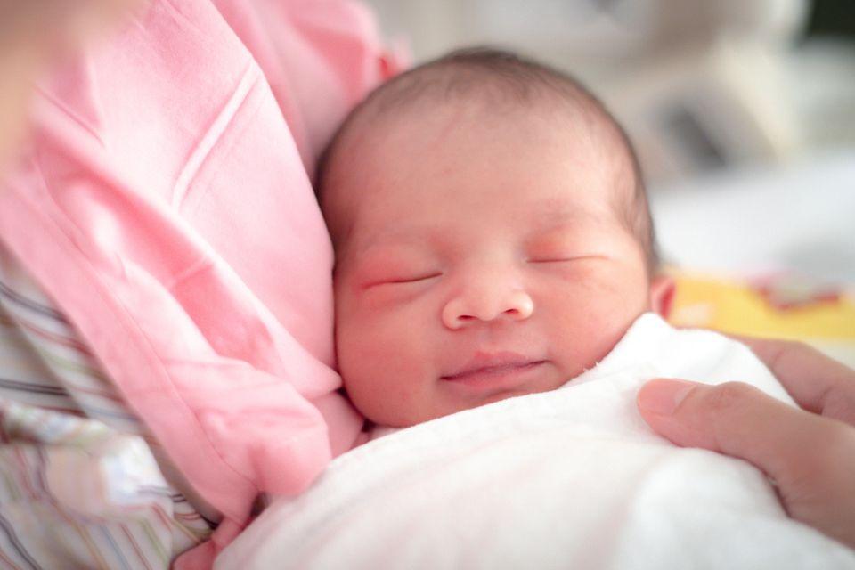 Neugeborenes lächelt im Schlaf
