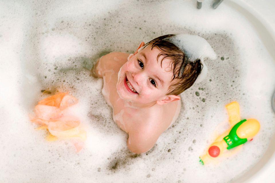 Junge sitzt in Badewanne und schaut nach oben