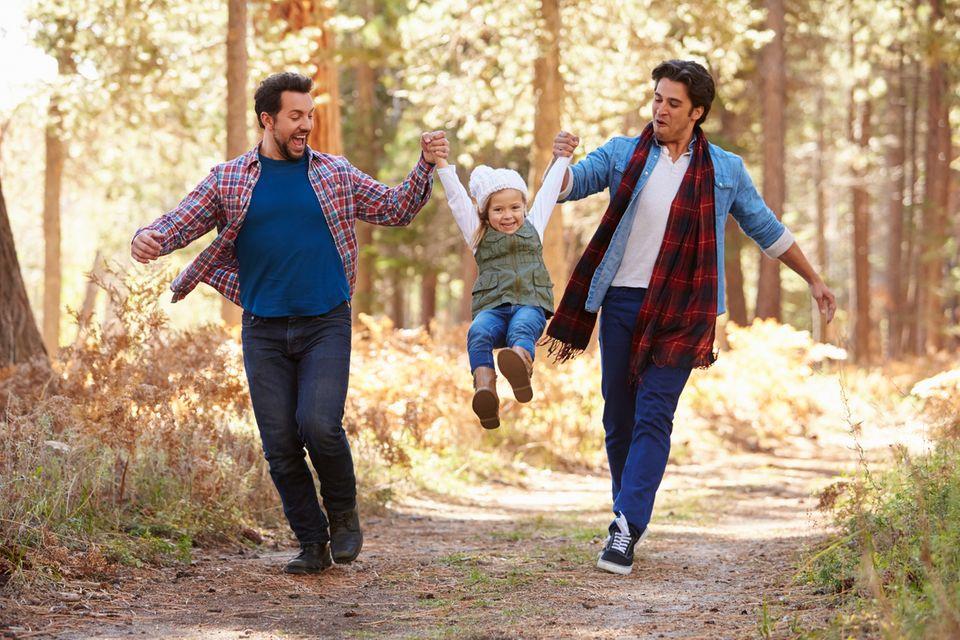 Zwei Väter laufen durch den Wald, halten die Tochter an den Händen zwischen sich