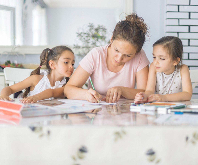 Mama und Kinder schreiben am Tisch