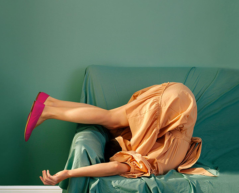 Frau macht auf einem Sofa eine Rolle rückwärts