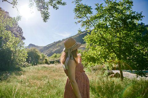 Schwangere steht in der Natur und schaut in die Ferne