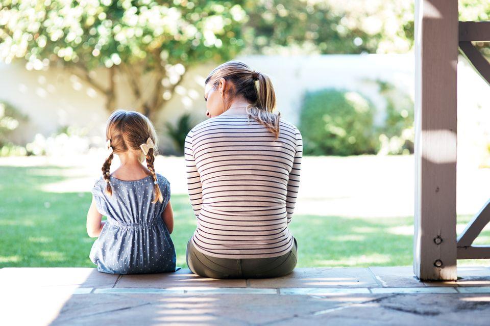 Mutter spricht mit Tochter auf Veranda
