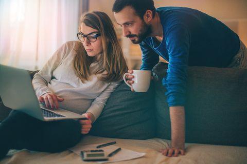Vater und Mutter auf der Couch füllen Formulare aus