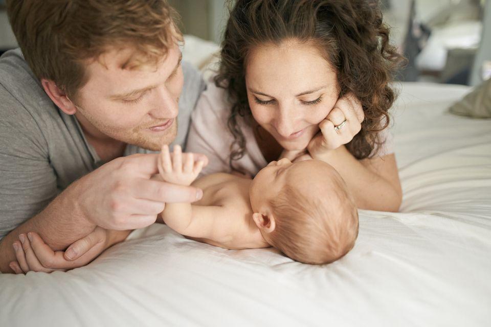 Eltern schauen auf dem Bett liegend ihr Baby an
