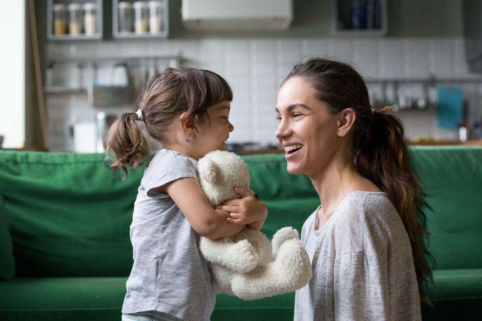 Mutter und Mädchen lächeln sich an