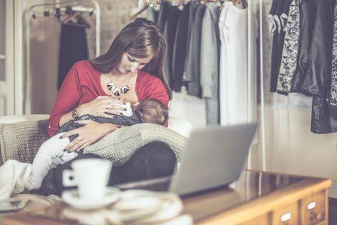 Mutter stillt Baby in der Wohnung mit Kaffee im Vordergrund