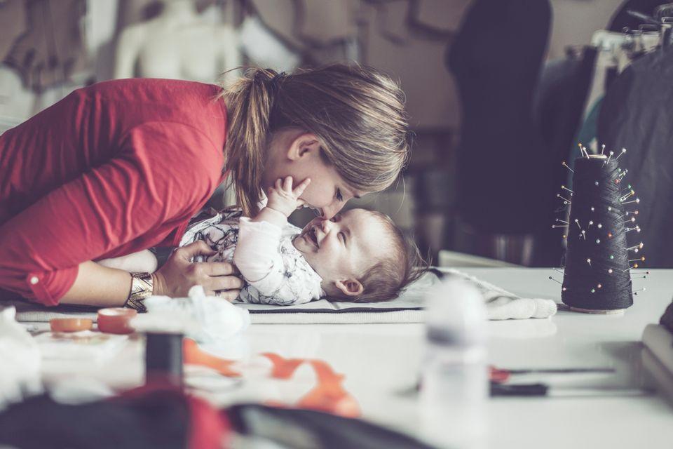 Mutter wickelt Baby und spielt mit ihm