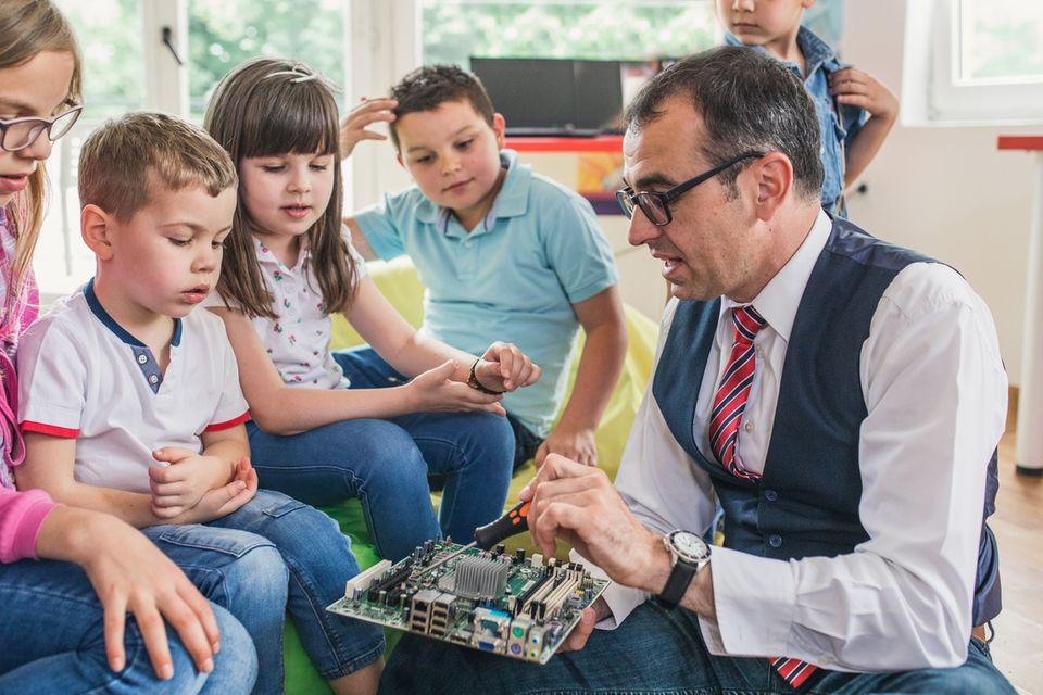 Betriebliche Kinderferienbetreuung, ein männlicher Lehrer unterrichtet Grundschulkinder in Computertechnik