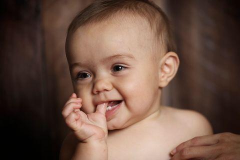 Suesses Baby mit den ersten Zaehnchen laechelt in die Kamera