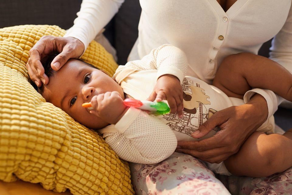 Baby mit Beißring wird von seiner Mama getröstet