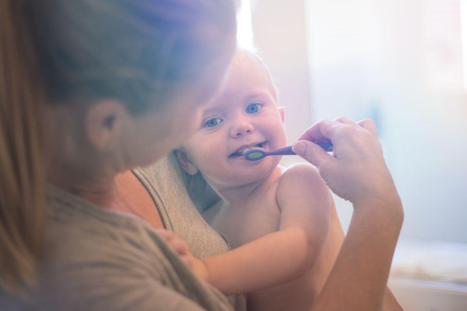 Mama hilft ihrem Baby beim Zähneputzen