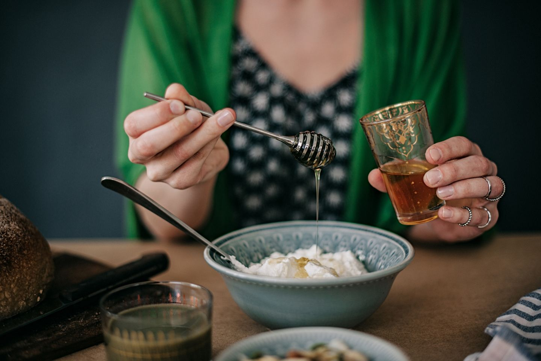 Frau tut einen Löffel Honig in ihren Joghurt